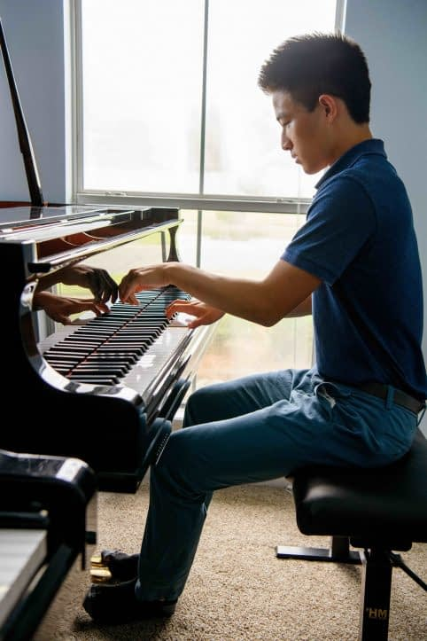 High school student playing piano